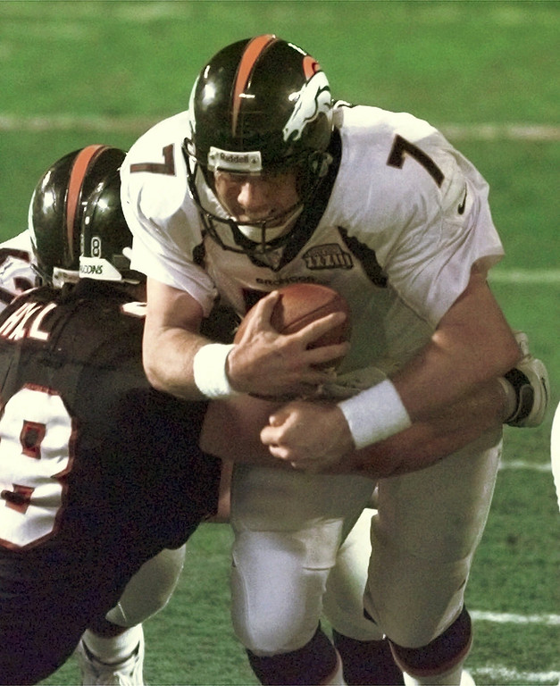 . Denver Broncos quarterback John Elway (7) drives for a touchdown as Atlanta Falcons\' Travis Hall (98) defends in the fourth quarter of Super Bowl XXXIII in Miami Sunday Jan. 31, 1999. The Broncos defeated the Falcons 34-19. Broncos Dan Neil, rear left obscured, is also in on the play.  (AP Photo/Bob Galbraith)