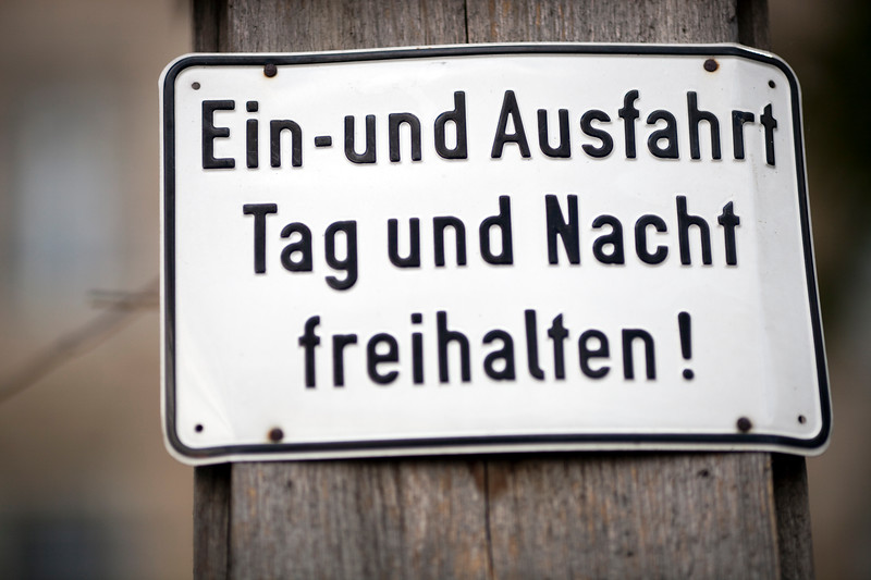 """No parking sign warning about keeping the space free day and night, Berlin, Germany. The sign says """"Ein-und Ausfahrt Tag und Nacht freihalten""""."""