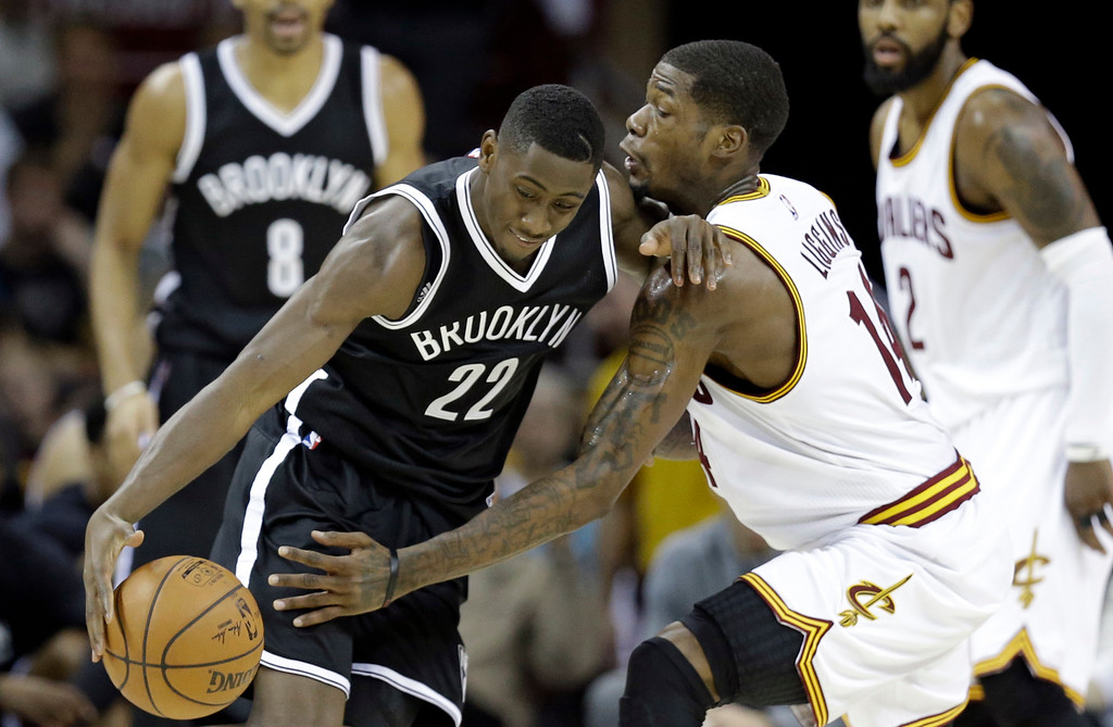 . Brooklyn Nets\' Caris LeVert (22) drives past Cleveland Cavaliers\' DeAndre Liggins (14) in the second half of an NBA basketball game, Friday, Dec. 23, 2016, in Cleveland. (AP Photo/Tony Dejak)