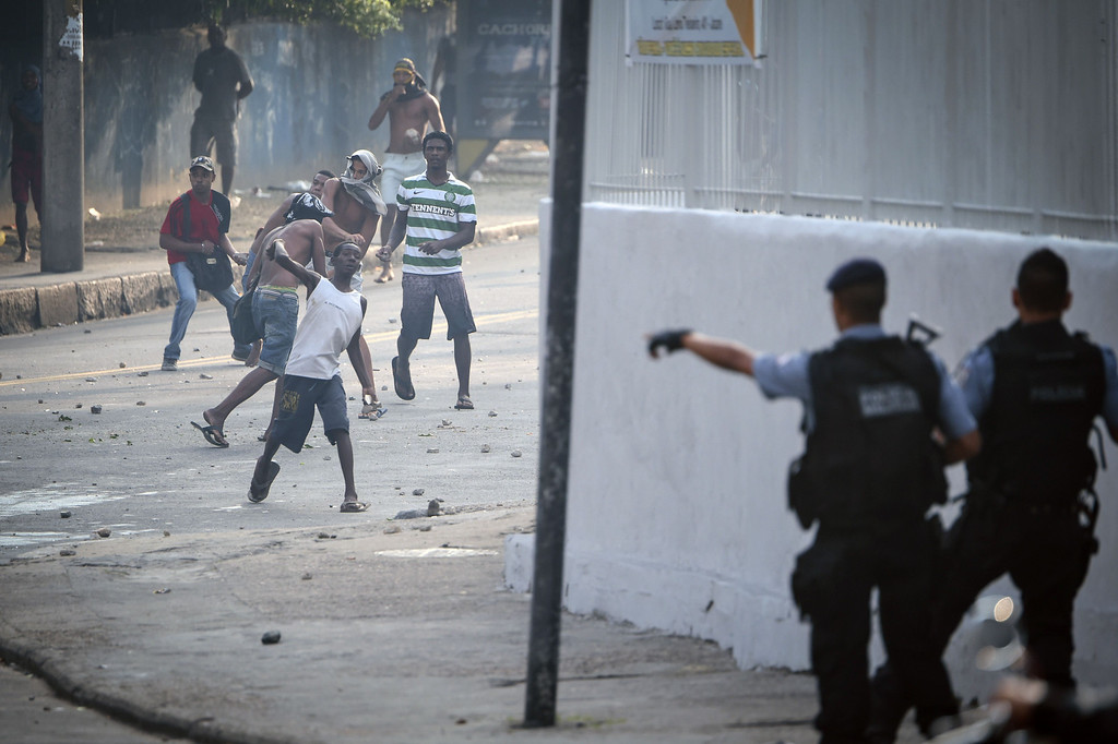 . Men throw stones at police that entered an abandoned building occupied by squatters to evict them in Rio de Janeiro, Brazil, on April 11, 2014. The lot, owned by a telephone company, included offices and warehouses and was occupied last week. AFP PHOTO/YASUYOSHI CHIBAYASUYOSHI CHIBA/AFP/Getty Images