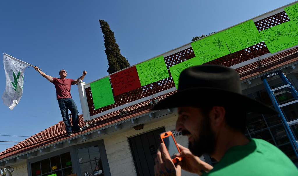 . George Lanzas, 33, of Hesperia and the manager of Doc Holliday\'s Collective, in Mentone, uses his phone to photograph the collectives\' owner, Luke Luce, as supporters protest the closure of the medical marijuana dispensary Monday August 12, 2013.  (Photo by Rick Sforza/Redlands Daily Facts)