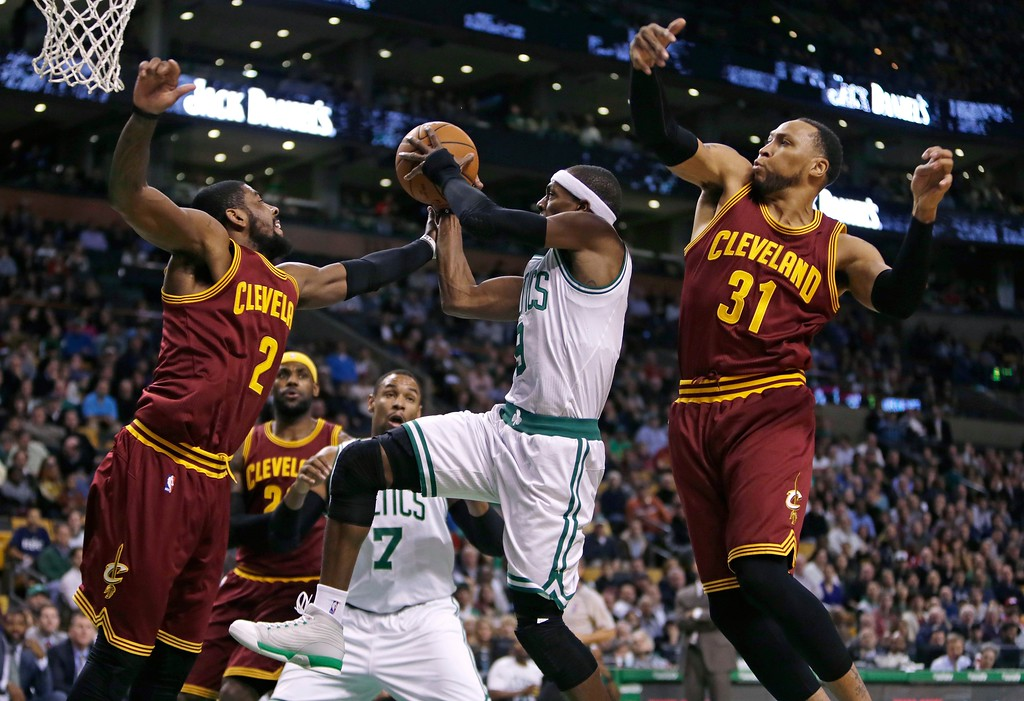 . Boston Celtics guard Rajon Rondo, center, threads between Cleveland Cavaliers forward Shawn Marion (31) and guard Kyrie Irving (2) on a drive to the basket during the first quarter of an NBA basketball game in Boston, Friday, Nov. 14, 2014. (AP Photo/Charles Krupa)