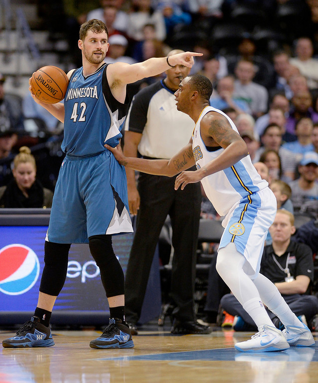 . Kevin Love (42) of the Minnesota Timberwolves calls out a play as Darrell Arthur (00) of the Denver Nuggets defends during the second quarter at the Pepsi Center.  (Photo By AAron Ontiveroz/The Denver Post)