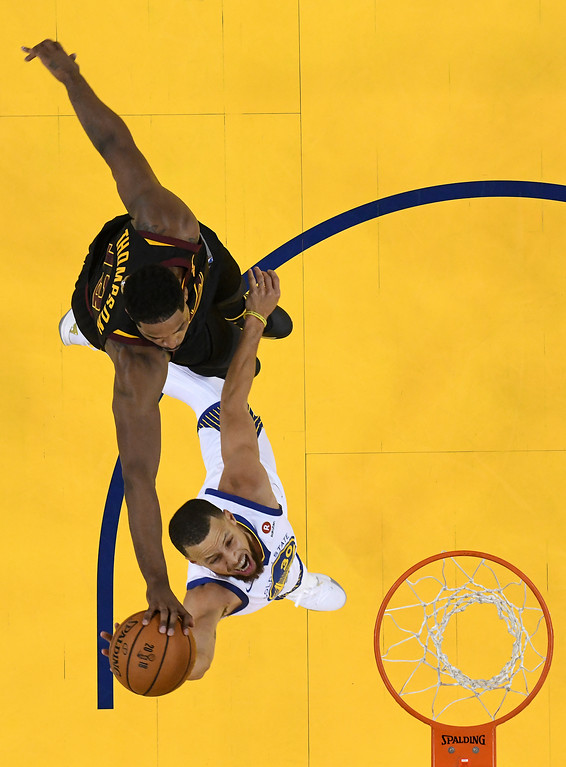 . Cleveland Cavaliers center Tristan Thompson, top, blocks a shot by Golden State Warriors guard Stephen Curry during the first half of Game 1 of basketball\'s NBA Finals in Oakland, Calif., Thursday, May 31, 2018. The Warriors won 124-114 in overtime. (Kyle Terada/Pool Photo via AP)