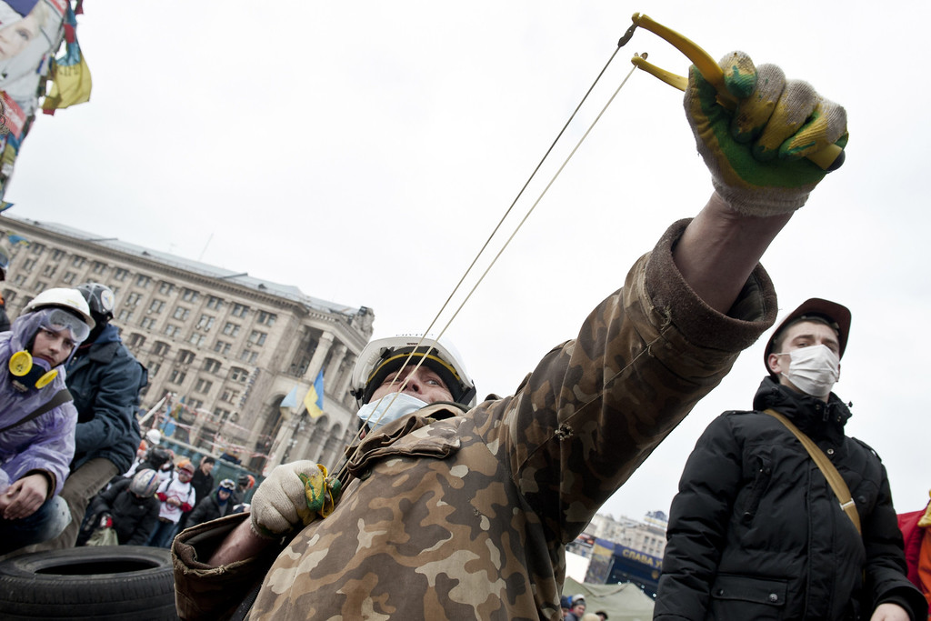 . An anti-government protester uses a slingshot to throw stones towards riot police on Kiev\'s Independence square on February 19, 2014.   AFP PHOTO / PIERO  QUARANTA/AFP/Getty Images