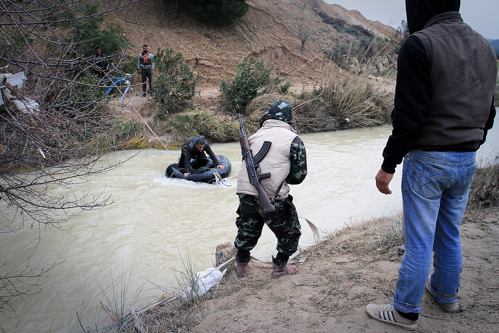 . This photograph taken on February 23, 2012 shows members of the Free Syrian Army moving weapons, medicine and personnel across a river near Al Janoudiyah, in the Idlib province of Syria.  Syrian regime forces killed 11 civilians and wounded 28 others on Monday, after more than 150 people were killed in violence over the weekend, a monitoring group said. The Britain-based monitoring group said explosions shook the Homs neighbourhoods of Hamidiyeh, Bustan al-Diwan, and the city centre. Two others were killed when a rocket fired by regime troops hit a car in which they travelled in the village of Talheya, in the northern province of Idlib, the Observatory said. ENN-Bradley Secker/AFP/Getty Images