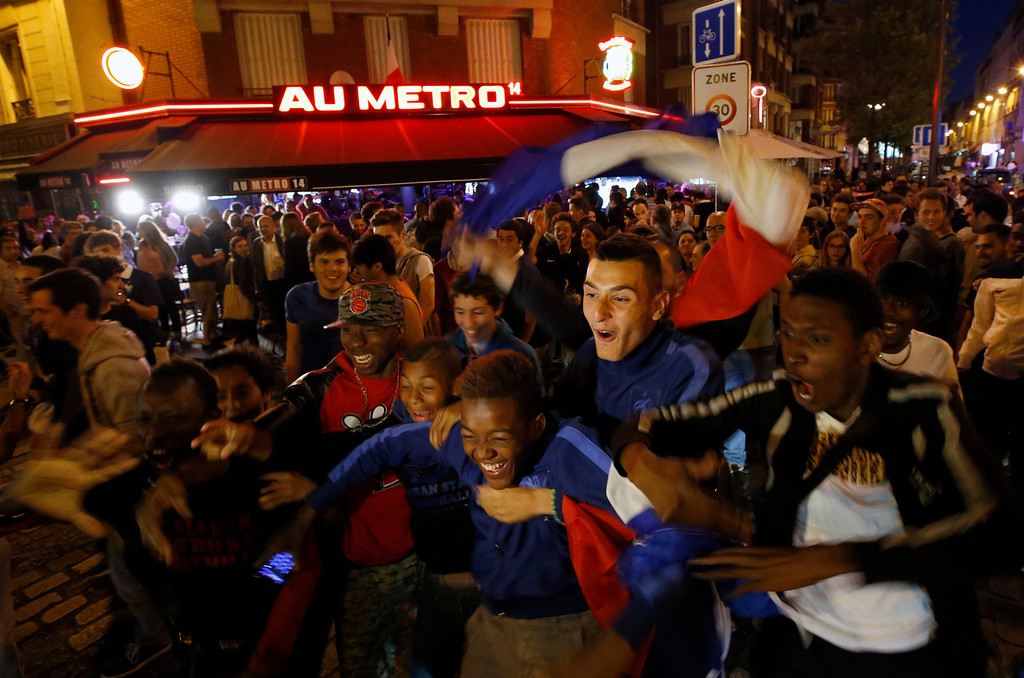 . French soccer supporters react as they watch a live broadcast of the group E World Cup soccer match between Switzerland and France, at the Metro 14th District bar in Paris, France, Friday, June 20, 2014. The match ended in a 5-2 win for France. (AP Photo/Francois Mori)