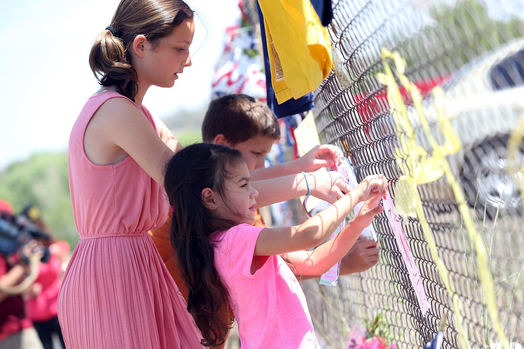 . Thirteen-year-old Trinity Walker(L) puts up handwritten notes with Cole Walker, 11 and Skyler Teeters, 4, at the memorial for the 19 fallen Granite Mountain Hotshot firefighters outside of fire station 7 in Prescott, Arizona July 2, 2013. Teeters mother went to school with several of the firefighters.  AFP PHOTO / KRISTA  Kennell/AFP/Getty Images