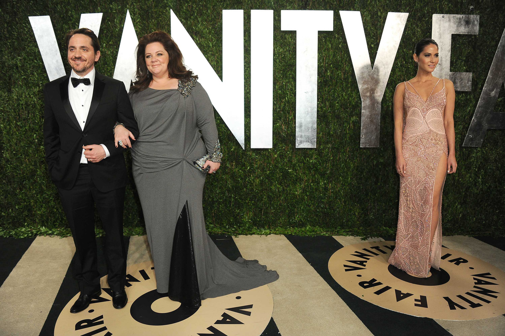 . Actor Ben Falcone, left, actress Melissa McCarthy and actress Olivia Munn, right, arrive at the 2013 Vanity Fair Oscar party on Sunday, Feb. 24 2013 at the Sunset Plaza Hotel in West Hollywood, Calif. (Photo by Jordan Strauss/Invision/AP)