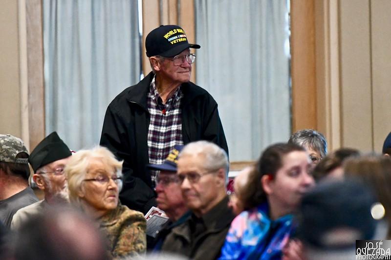 A World War II veteran stands to applause.
