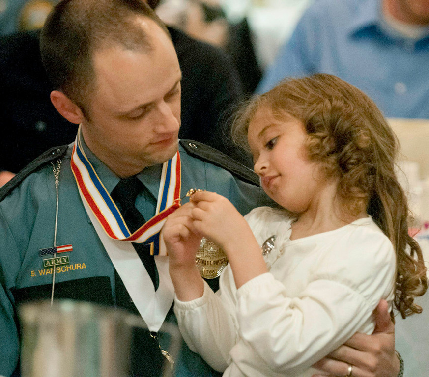 . Ella Wanschura, 5, checks out the two medals her father, Brian Wanschura, received Thursday, May 2, 2013, at a ceremony honoring St. Paul police officers. St. Paul Police Chief Thomas Smith presented Wanschura and his partner, Dan King, with Officer of the Year awards. They were also awarded the Medal of Valor. (Pioneer Press: Chris Polydoroff)