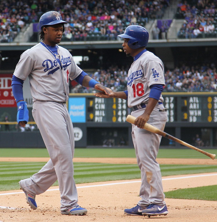 . Los Angeles Dodgers\' Hanley Ramirez, left, is congratulated by teammate Chone Figgins after the pair scored on a triple by Matt Kemp against the Colorado Rockies in the first inning of a baseball game in Denver on Sunday, June 8, 2014. (AP Photo/David Zalubowski)
