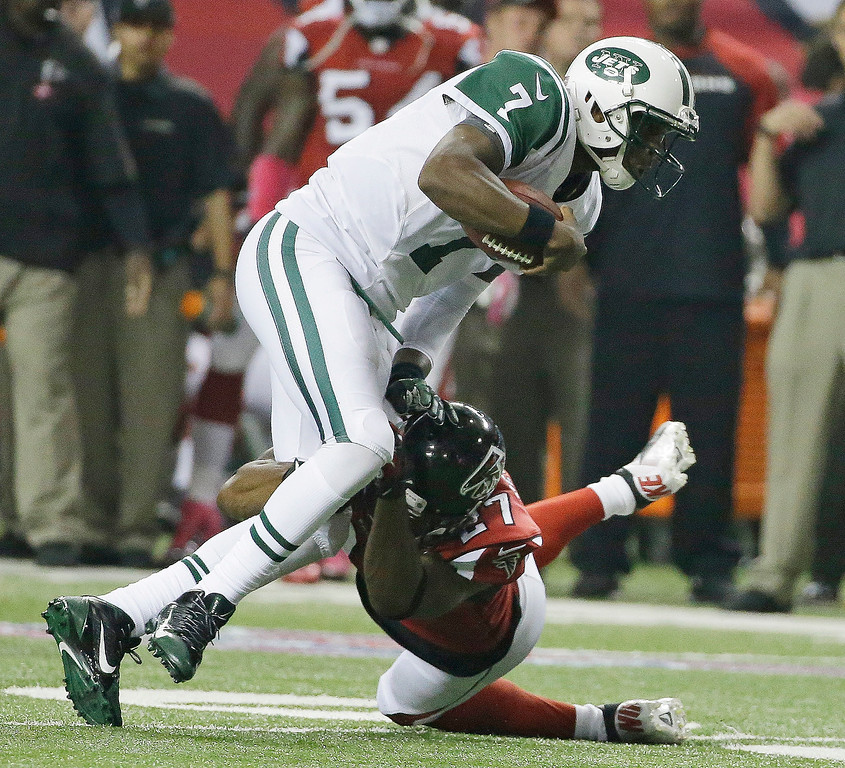 . New York Jets quarterback Geno Smith (7) his hit in the open field by Atlanta Falcons cornerback Robert McClain (27) during the second half of an NFL football game, Monday, Oct. 7, 2013, in Atlanta. (AP Photo/David Goldman)