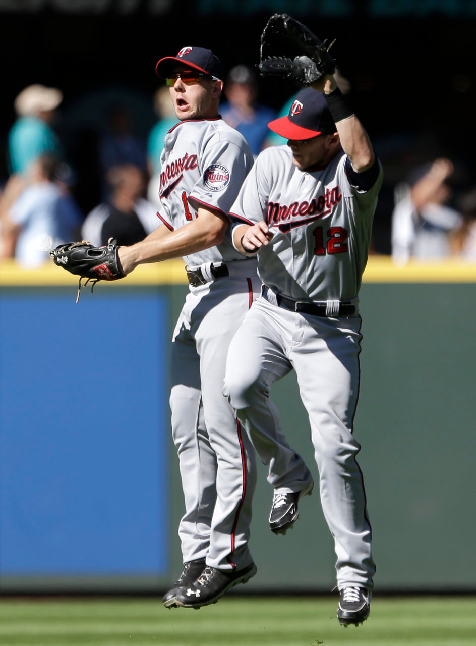 . Minnesota Twins outfielders Clete Thomas, left, and Chris Herrmann celebrate after the team defeated the Seattle Mariners. (AP Photo/Elaine Thompson)