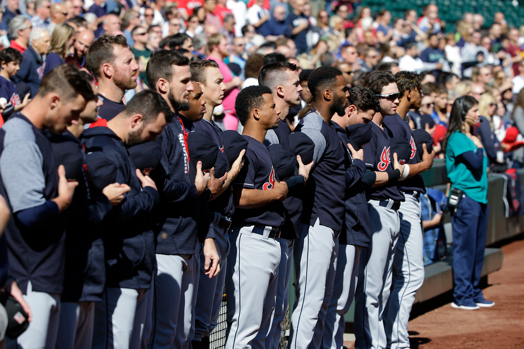 . Cleveland Indians players and coaches stand during the singing of the national anthem before a baseball game against the Seattle Mariners, Sunday, Sept. 24, 2017, in Seattle. (AP Photo/Ted S. Warren)