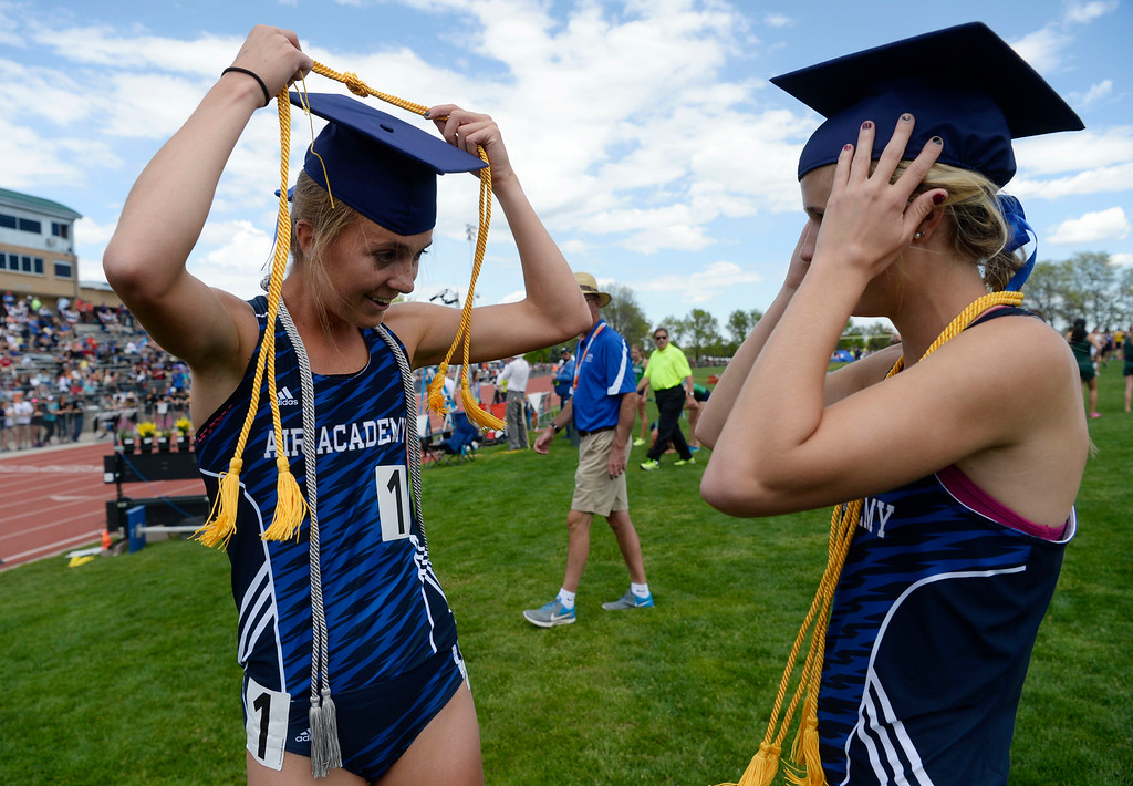 . LAKEWOOD, CO - May 19: Air Academy 4A 4x800 meter relay champions Katie Rainsberger, left, and teammate Kayla Wiitala, both seniors, sport their graduation caps after at the Colorado State High School Track and Field Championships at Jeffco Stadium May 19, 2016. Graduation was being held in Colorado Springs at the same time as the 4x800 relay event that they won. (Photo by Andy Cross/The Denver Post)