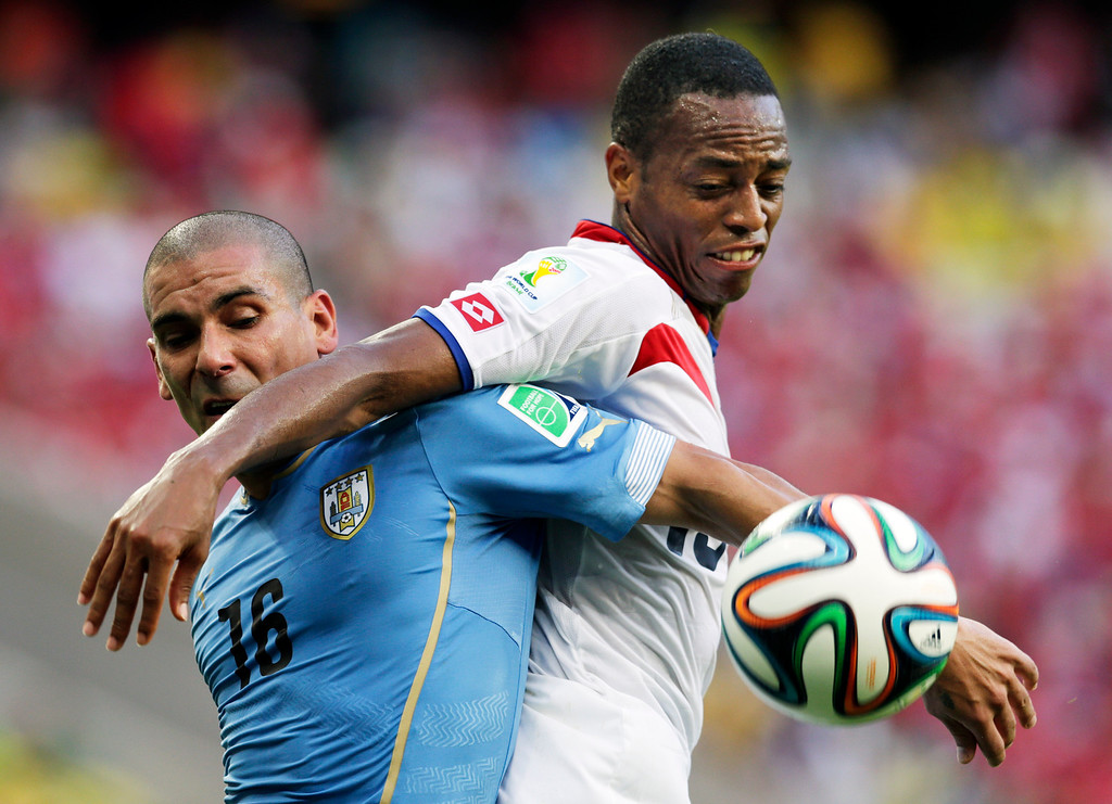 . Uruguay\'s Maxi Pereira (16) struggles with Costa Rica\'s Junior Diaz during the group D World Cup soccer match between Uruguay and Costa Rica at the Arena Castelao in Fortaleza, Brazil, Saturday, June 14, 2014.  (AP Photo/Fernando Llano)