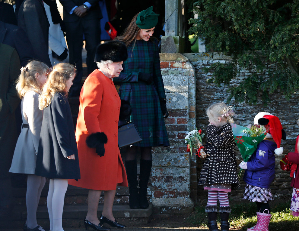 . Britain\'s Queen Elizabeth II receives flowers from children as the Duchess of Cambridge, top, looks on after members of the royal family attended a Christmas Day Service at St. Mary\'s church on the grounds of Sandringham Estate, the Queen\'s royal estate in Norfolk, England, Wednesday, Dec. 25, 2013. (AP Photo/Lefteris Pitarakis)
