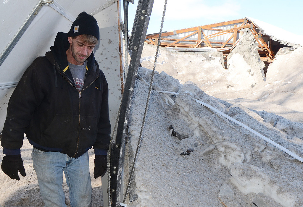 . Dusty DeCair looks over the ruins after the roof collapsed Tuesday, Feb. 11, 2014 morning at his consignment shop in Marshall Township, Mich. DeCair lost tools, air compressors, fountains, seasonal items, shelving and more during the Tuesday collapse in Marshall Township.  Snow is being blamed for the collapse.  (AP Photo/The Enquirer, John Grap)