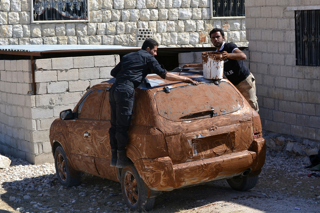 . Rebel fighters cover a car in mud for camouflage at an undisclosed location in Syria\'s northwestern province of Idlib on October 8, 2013. The world\'s chemical watchdog said it will send a second team of inspectors to help dismantle Syria\'s arsenal, as regime warplanes bombed rebels in the northwest of the country.  MOHAMAD JADAAN/AFP/Getty Images