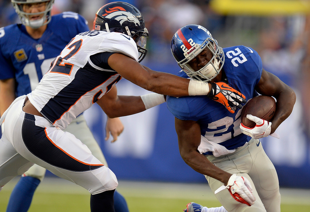 . Denver Broncos outside linebacker Wesley Woodyard (52) grabs New York Giants running back David Wilson (22) up around the neck as he tackles him during the second quarter September 15, 2013 MetLife Stadium. (Photo by John Leyba/The Denver Post)