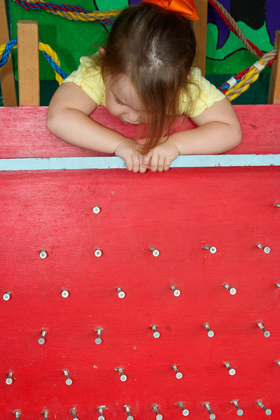 Watching her ball go down the peg board