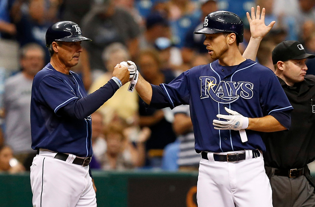 . Tampa Bay\'s Ben Zobrist, right, is congratulated by third base coach Tom Foley after his triple during the seventh inning against the Twins. Zobrist scored on the next play with what proved to be the winning run. (AP Photo/Mike Carlson)
