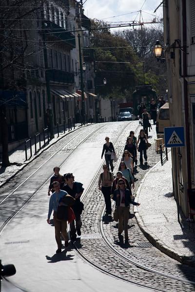 Visitors walking down a typical Alfama street, Lisbon, Portugal