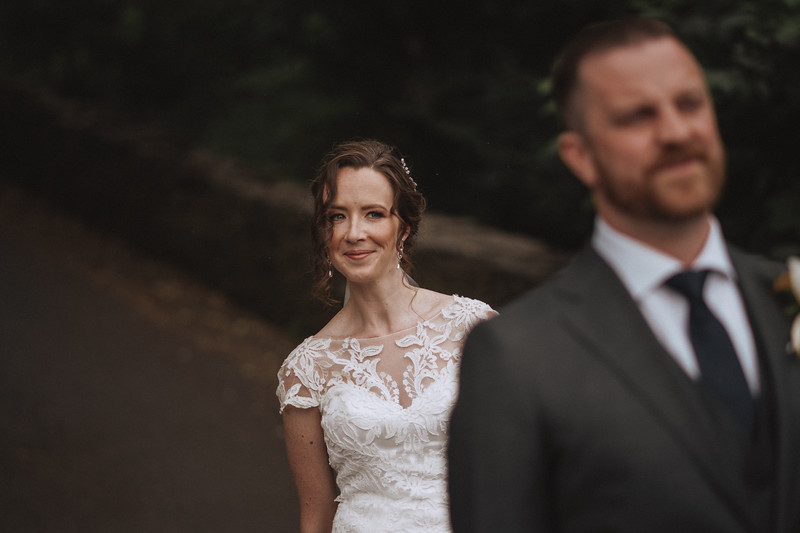 The bride looking over the grooms shoulder with a big smile on her face.