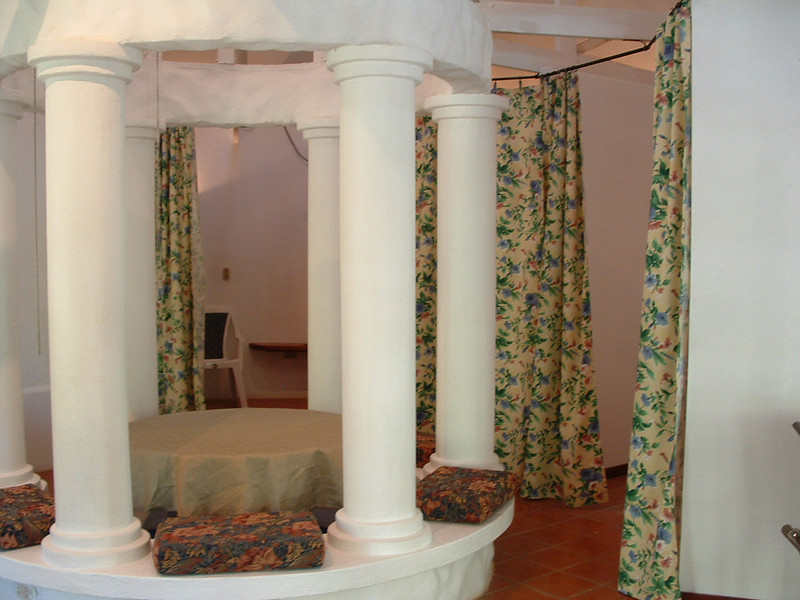 It's a round house with columns in the center with a dining table & banquets set inside & the rooms are built around it!!  Quite unique!