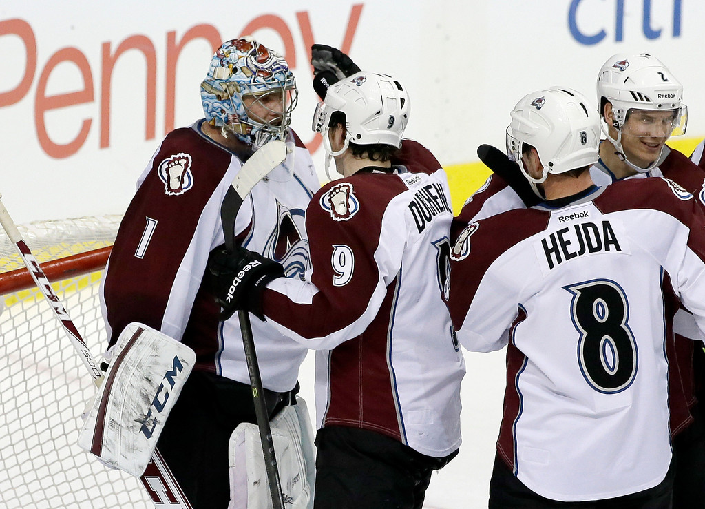 . Colorado Avalanche goalie Semyon Varlamov (1), of Russia, is congratulated by Matt Duchene (9), Jan Hejda (8), of Czech Republic, and Nick Holden (2) following an NHL hockey game against the Dallas Stars, Monday, Jan. 27, 2014, in Dallas. Varlamov made 41 saves in the 4-3 Avalanche win. (AP Photo/Tony Gutierrez)