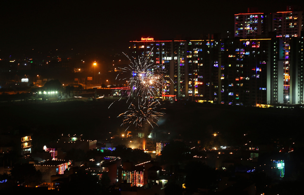 . Residential buildings are decorated with colorful lights, as a firecracker lights up, during Diwali festival in New Delhi, India, Thursday, Oct. 19, 2017. Worried especially by the impact on the health of children, the Supreme Court this year banned the sale of firecrackers, that is usually in huge demand across the country as the evening sky is lit up by the festivities, in the Indian capital and neighboring areas to prevent a toxic haze after the Diwali nights that has residents hiding indoors. (AP Photo/Altaf Qadri)