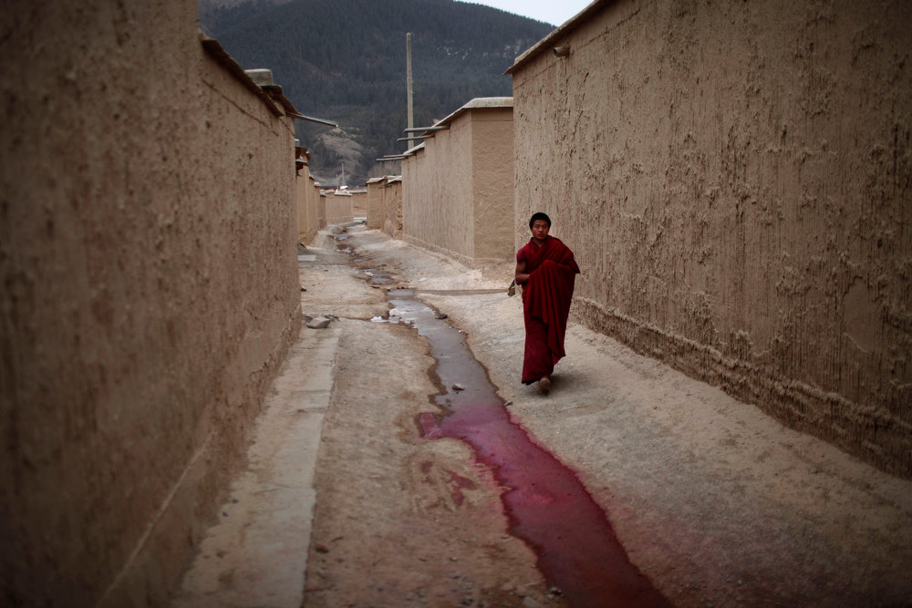 Description of . A Tibetan monk walks along an alley at Labrang Monastery during Tibetan new year, in Xiahe county, Gansu Province, February 11, 2013. Tibetans in a northwest part of China which has been a focus of self-immolation protests against Chinese rule marked a low-key lunar New Year on Monday, with many saying celebrations were inappropriate while the burnings continued. At least 20 people have set themselves on fire in the region around Xiahe in Gansu province over the last year, according to exiles and rights groups. Xiahe is home to a large ethnically Tibetan population and also to the monastery at Labrang, one of the most important centres for Tibetan Buddhism. The Tibetan lunar new year is supposed to be a time for celebration, but many Tibetans who spoke to Reuters in Xiahe said there would be no entertainment this year.  REUTERS/Carlos Barria