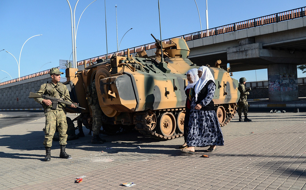 . Women walk past Turkish soldiers standing guard by their armoured vehicle in downtown Diyarbakir on October 8, 2014. The Turkish army has deployed in the streets of Diyarbakir to impose a curfew, following violent protests by pro-Kurdish demonstrators in southeast Turkey angry at the government\'s lack of action against jihadists in Syria, officials said on October 8, 2014. At least 14 people were killed, 8 of the deaths came in Turkey\'s main Kurdish city of Diyarbakir where the most intense rioting took place overnight. AYAS AKENGIN/AFP/Getty Images