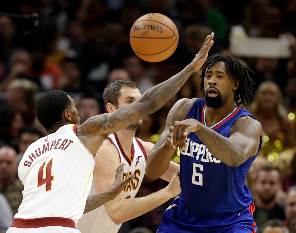 . Los Angeles Clippers\' DeAndre Jordan (6) passes against Cleveland Cavaliers\' Kevin Love (0) and Iman Shumpert (4) in the first half of an NBA basketball game, Friday, Nov. 17, 2017, in Cleveland. (AP Photo/Tony Dejak)