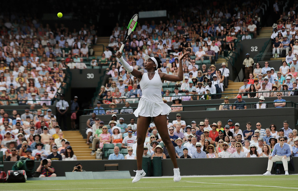 . Venus Williams of the US returns a ball to Alexandra Dulgheru of Romania during their women\'s singles match on the third day at the Wimbledon Tennis Championships in London, Wednesday July 4, 2018. (AP Photo/Ben Curtis)