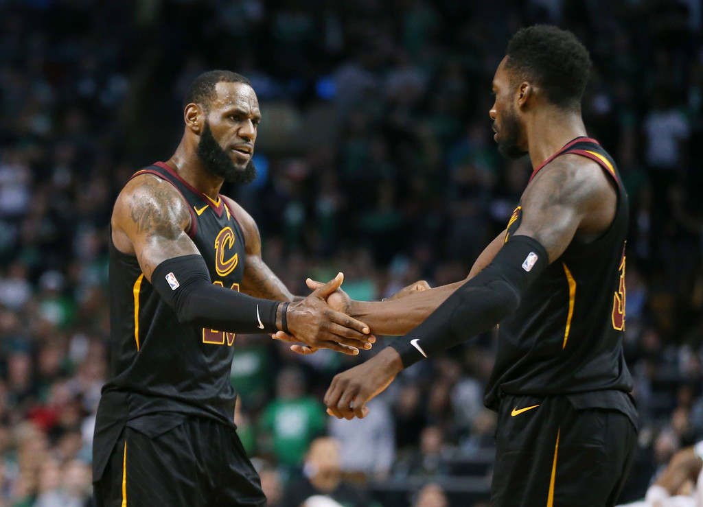 . Cleveland Cavaliers forwards LeBron James, left, and Jeff Green clasp hands during the second half in Game 7 of the NBA basketball Eastern Conference finals against the Boston Celtics, Sunday, May 27, 2018, in Boston. (AP Photo/Elise Amendola)