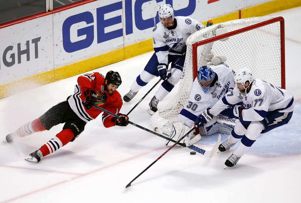 . Chicago Blackhawks\' Andrew Desjardins (11) tries to reach a puck as Tampa Bay Lightning goalie Ben Bishop (30), Anton Stralman (6), of Sweden, and Victor Hedman (77), of Sweden, defend during the first period in Game 6 of the NHL hockey Stanley Cup Final series on Monday, June 15, 2015, in Chicago. (AP Photo/Charles Rex Arbogast)