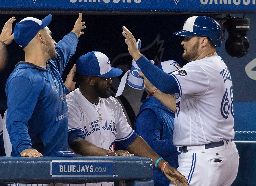 . Toronto Blue Jays\' Rowdy Tellez, right, gets high-fives in the dugout after hitting a double in the eighth inning of a baseball game against the Cleveland Indians on Thursday, Sept. 6, 2018, in Toronto. (Fred Thornhill/The Canadian Press via AP)