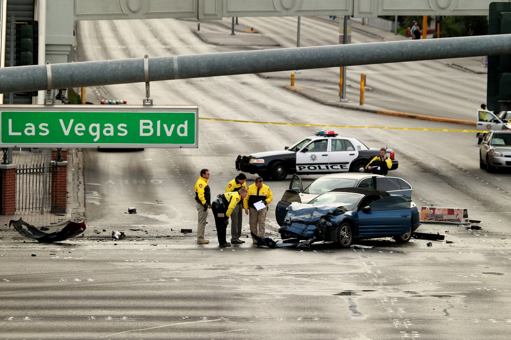 Description of . Law enforcement personal investigate the scene of a mulit-vehicle accident on Las Vegas Blvd and Flamingo Road Thursday, Feb. 21, 2013. Authorities say a Range Rover opened fire on a Maserati at a stoplight, sending it crashing into a taxi that went up in flames, leaving three people dead and at least six injured. Police were checking with nearby businesses to see whether a previous altercation prompted the car-to-car attack  (AP Photo/Las Vegas Review-Journal, Jeff Scheid)