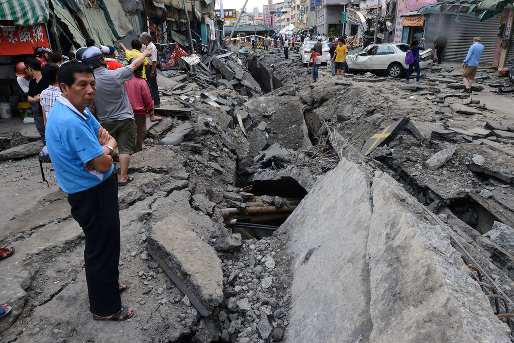 . A local resident looks at the damage caused by gas explosions in the southern Taiwan city of Kaohsiung on August 1, 2014. A series of powerful gas blasts killed at least 25 people and injured up to 267 in the southern Taiwanese city of Kaohsiung, overturning cars and ripping up roads as terrified residents fled an inferno.     AFP PHOTO  / SAM YEH/AFP/Getty Images