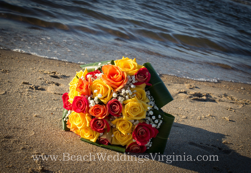 orange, yellow & peach roses with baby's breath bordered with tea leaves. Stems tied