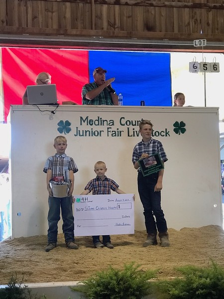 Logan, left, Colton and Austin Letner get ready to present their giant check and thank-you gifts to the buyers of Austins St. Jude Hog on Saturday at the Medina County Fair.  LYDIA MAINZER / GAZETTE