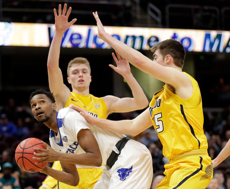 . Buffalo\'s Montell McRae, left to right, is stopped by Toledo\'s Jaelan Sanford and Toledo\'s Nate Navigato during the first half of an NCAA college basketball championship game of the Mid-American Conference tournament, Saturday, March 10, 2018, in Cleveland. (AP Photo/Tony Dejak)