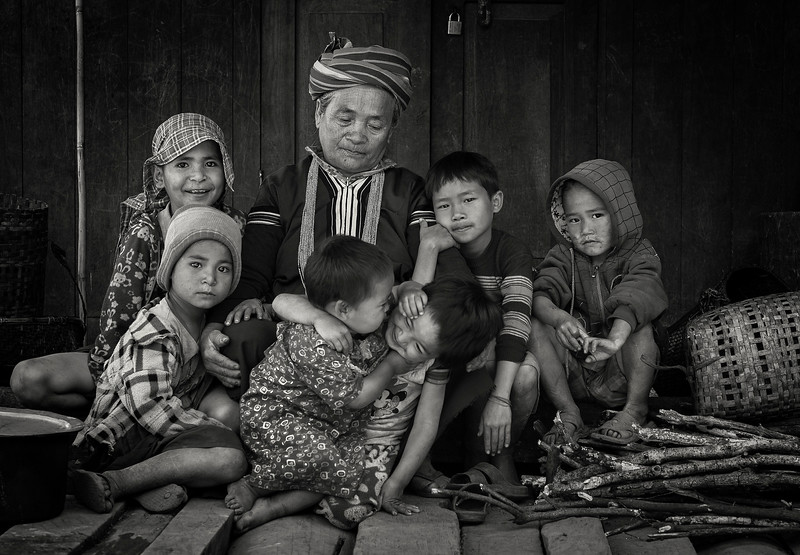 This is Shen Om and some of her grandchildren.  She is not exactly sure how many grandchildren she has.  After counting with her fingers for a while she gave up and explained that at least she was sure she had two sons and three daughters. When asked about her age she laughed and said she was around sixty. probably not.  Chin State, Myanmar, 2017.