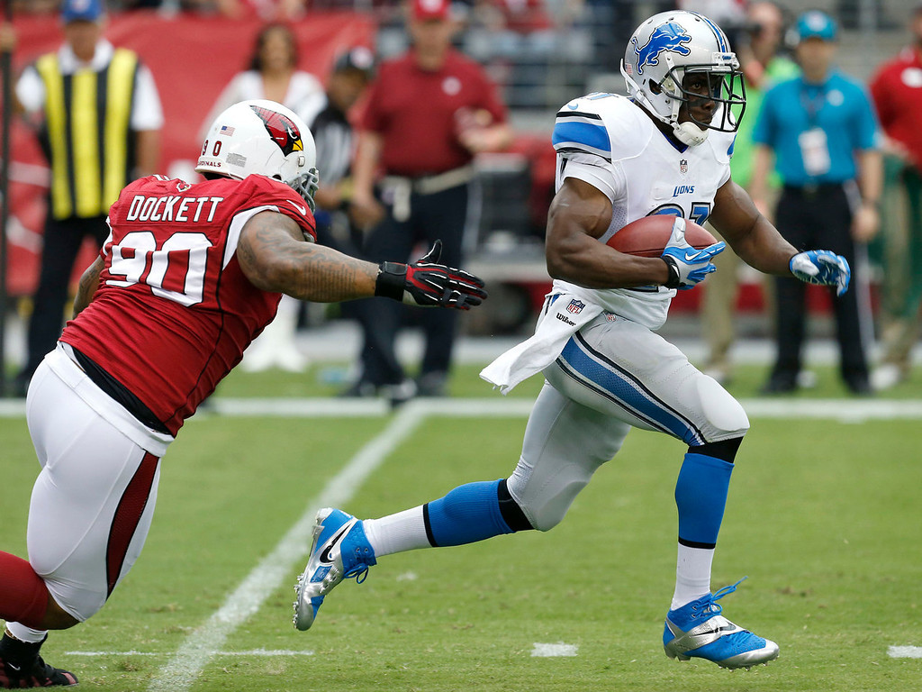 . Detroit Lions running back Reggie Bush escapes the reach of Arizona Cardinals defensive end Darnell Dockett (90) during the first half of a NFL football game, Sunday, Sept. 15, 2013, in Glendale, Ariz. (AP Photo/Ross D. Franklin)