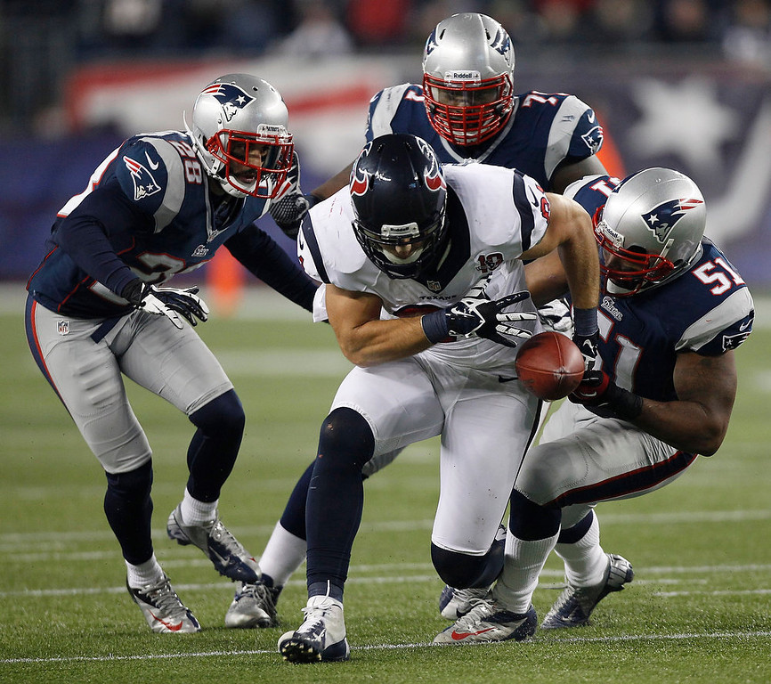 . Houston Texans tight end Owen Daniels loses the ball while being stopped by New England Patriots\' Steve Gregory, Brandon Deaderick and Jerod Mayo during the second half of an AFC divisional playoff NFL football game in Foxborough, Mass., Sunday, Jan. 13, 2013. The play had been stopped before Daniels dropped the ball. (AP Photo/Stephan Savoia)