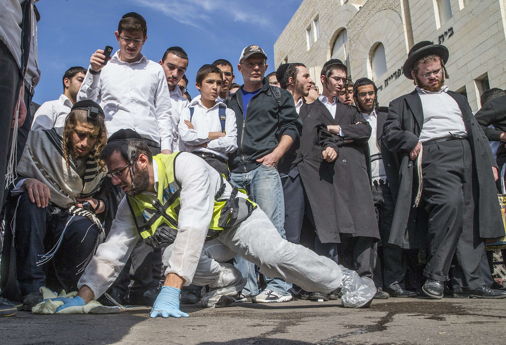 . An Israeli emergency services member cleans the sidewalk at the scene of an attack, by two Palestinians, on Israeli worshippers at a synagogue in the ultra-Orthodox Har Nof neighborhood in Jerusalem on November 18, 2014. AFP PHOTO / JACK GUEZ/AFP/Getty Images