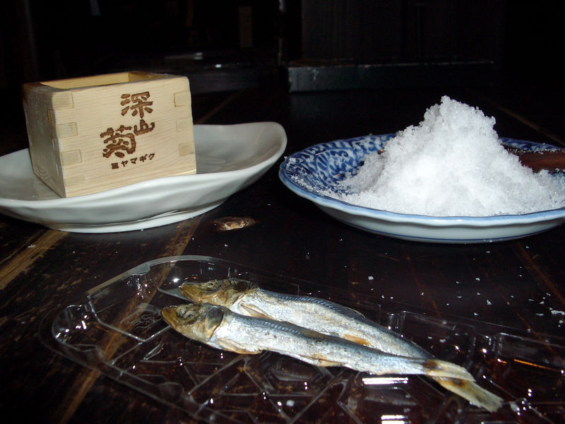 Sake (in wooden box) with snacks and salt.