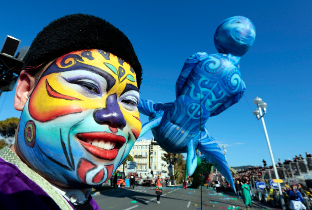 ". An artist drags a giant balloon during the Carnival parade in Nice February 16, 2013. The 129th Carnival of Nice runs from February 15 to March 6 and celebrates the ""King of the Five Continents\"".       REUTERS/Eric Gaillard"